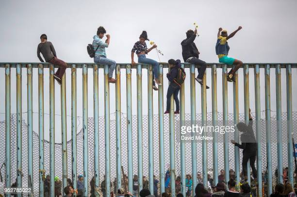 People climb a section of border fence to look toward supporters in the U.S. As members of a caravan of Central American asylum seekers arrive to a...