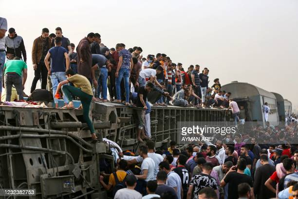 People climb an overturned train carriage as they gather at the scene of a railway accident in the city of Toukh in Egypt's central Nile Delta...