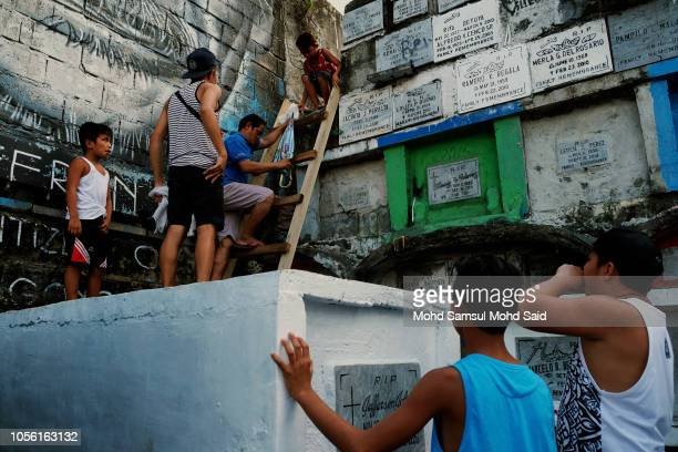 People climb atop of tombs in a cemetery during the commemoration of All Saints' Day in Manila on November 1 2018 in Manila Philippines Filipinos...