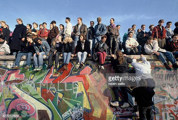 People climb onto the Berlin Wall on November 10th the morning after the announcement by the East German government that they would start granting...