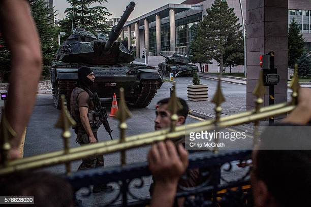 People climb the fence and yell at government aligned military personel who were involved in an action to arrest suspected coup plotters at the Army...