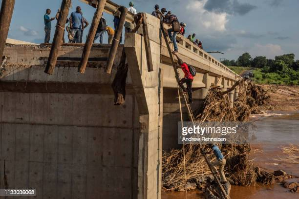 People climb to the top of a broken bridge damaged during Cyclone Idai across the Lucite River on March 26 outside of Magaro Mozambique The storm...