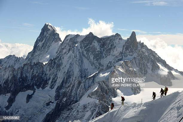 People climb to the top of the Aiguille du Midi a 3800 meters peak in the French Alps on September 16 2010 Backround are the Grandes Jorasses AFP...