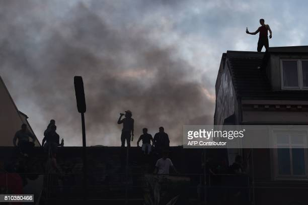 TOPSHOT People climb up on a roof to get a view during riots on July 7 2017 in Hamburg northern Germany where leaders of the world's top economies...