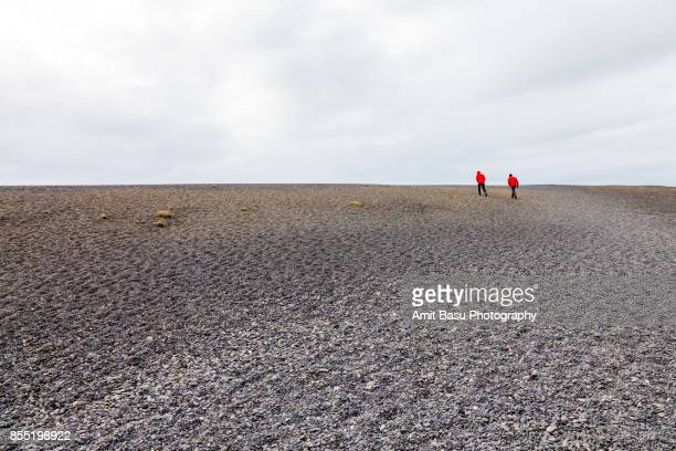 People climbing black rock beach dunes near Hvalnes Lighthouse, IcelandIceland