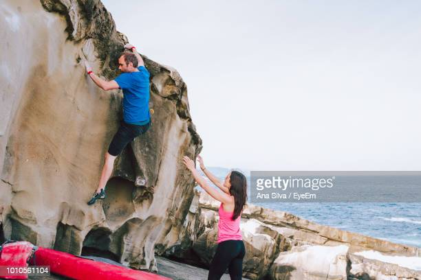 People Climbing On Rock At Beach Against Sky