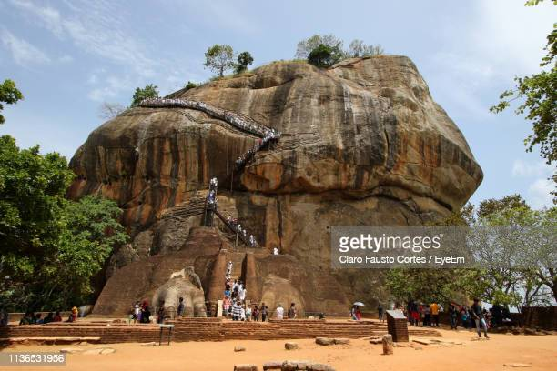 people climbing on rock formation - sigiriya stock photos and pictures