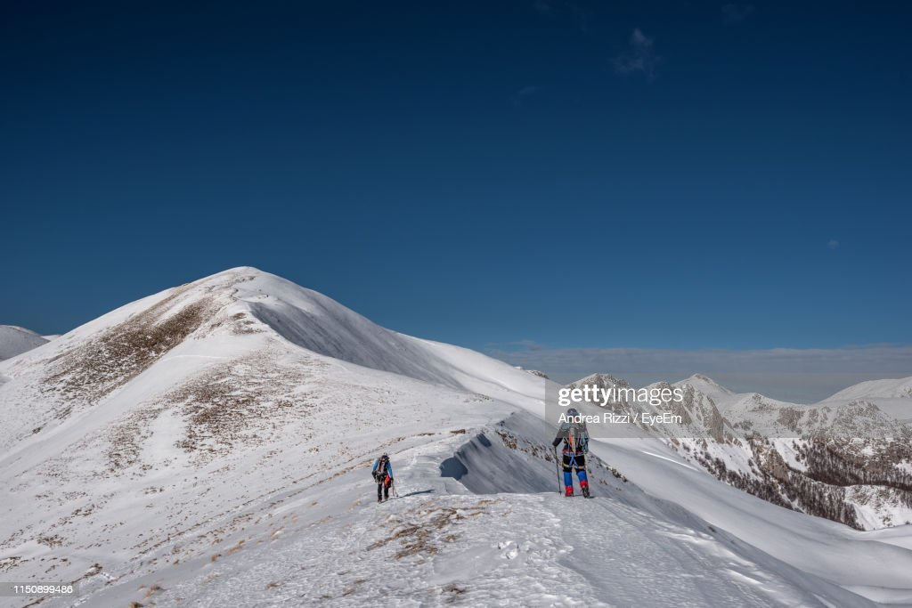 People Climbing On Snowcapped Mountain Against Clear Sky : Foto de stock