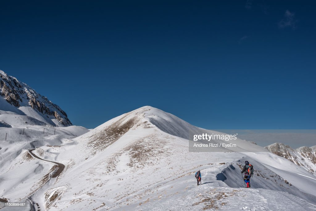People Climbing On Snowcapped Mountain Against Clear Sky : Foto stock