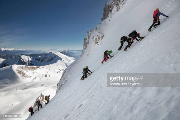 people climbing on snowcapped mountains during winter - andrea rizzi stockfoto's en -beelden