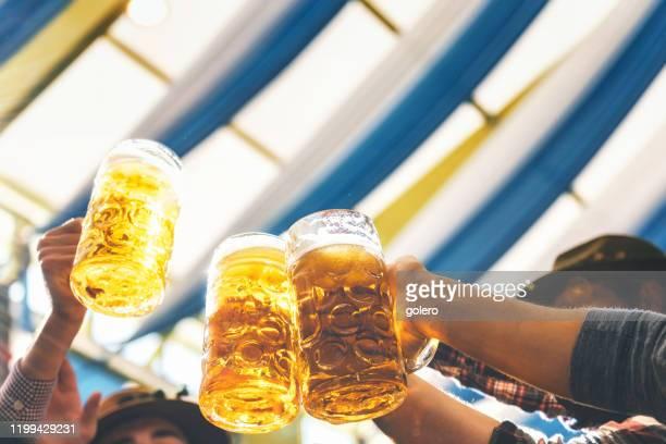 personas clinking gafas de cerveza de masaen sesión en oktoberfest en munich - oktoberfest fotografías e imágenes de stock