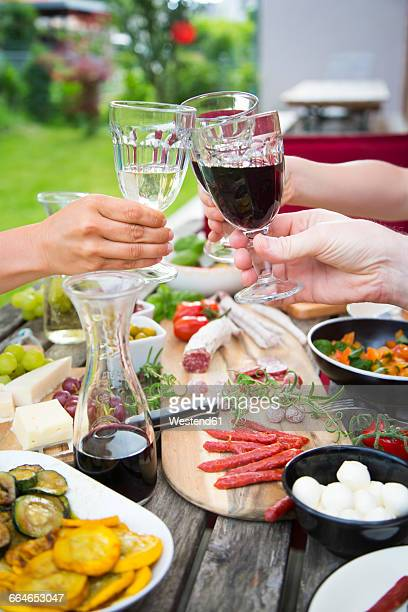 People clinking wine glasses and enjoying variety of Mediterranean antipasti in garden