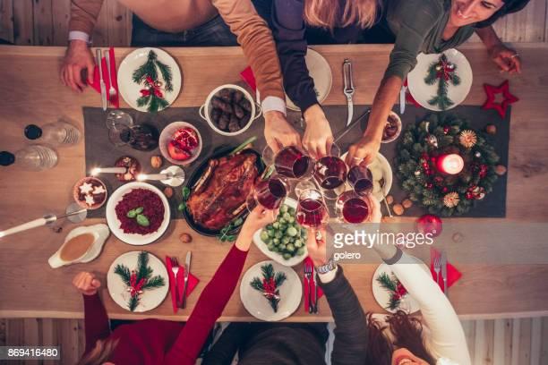 vasos de vino que tintinea personas en la mesa de navidad - christmas fotografías e imágenes de stock