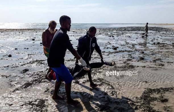 TOPSHOT People collect bodies on January 30 along a beach in Obock Djibouti after two migrant boats capsized off the coast The death toll from the...