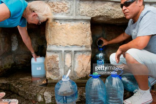 People collect drinking water from pipes fed by an underground spring in St James about 25km from the city centre on January 19 in Cape Town Cape...