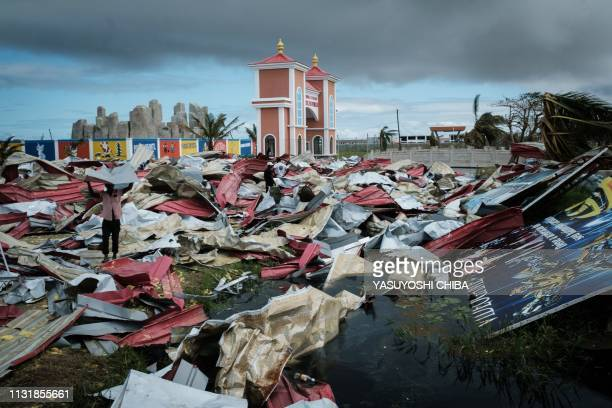 People collect metal sheets from a damaged supermarket to re-build their destroyed houses following the devastation caused by Cyclone Idai in Beira,...