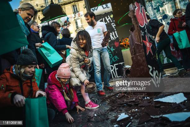 People collect pieces of a wall made with chocolate by French chocolate maker Patrick Roger to commemorate the 30th anniversary of the fall of the...