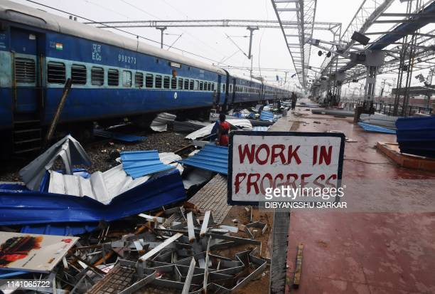 People collect pieces of debris next on the train tracks at the damaged railway station in Puri in the eastern Indian state of Odisha on May 4 after...