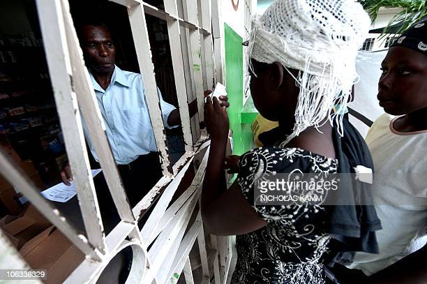People collect rehydration medecine for relatives suffering from cholera from the pharmacy at the Charles Colimon hospital in Petite Riviere on the...