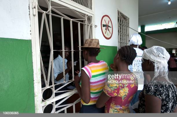 People collect rehydration medicine for relatives suffering from cholera from the pharmacy at the Charles Colimon hospital in Petite Riviere on the...