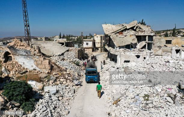 People collect scrap steel rods from the rubble and destruction in the aftermath of aerial bombardment in the town of Ihsim in Syria's rebel-held...