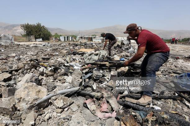 People collect the remains of fire that broke out on Sunday at Qob Elias refugee camp in Beqaa Lebanon on July 3 2017 Refugees reported that...