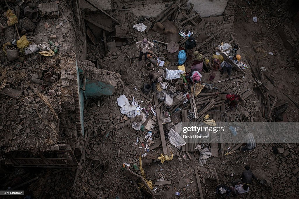 People collect their belongings among debris of a damaged building on May 3, 2015 in Bhaktapur, Nepal. A major 7.8 earthquake hit Kathmandu mid-day on Saturday, and was followed by multiple aftershocks that triggered avalanches on Mt. Everest that buried mountain climbers in their base camps. Many houses, buildings and temples in the capital were destroyed during the earthquake, leaving over 6000 dead and many more trapped under the debris as emergency rescue workers attempt to clear debris and find survivors. Regular aftershocks have hampered recovery missions as locals, officials and aid workers attempt to recover bodies from the rubble.