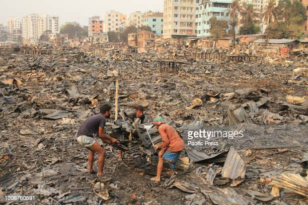 People collect their belongings from the ashes after a fire broke out at Shialbari side of Jhilpar slum area Hundreds of shanties were razed to the...