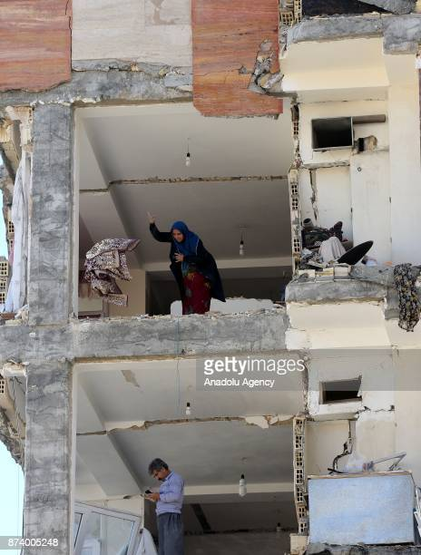 People collect their usable goods and belongings in their heavily damaged buildings in Sarpole Zahab town of Kermanshah Iran on November 14 2017...