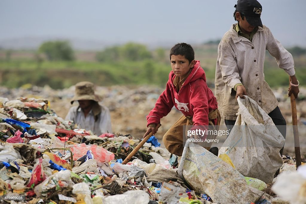 People collect usable material from a dump site on the World Environment Day in Islamabad, Pakistan on June 5, 2015. World Environment Day (WED) is celebrated every year on 5 June to raise global awareness to take positive environmental action to protect nature and the planet Earth.