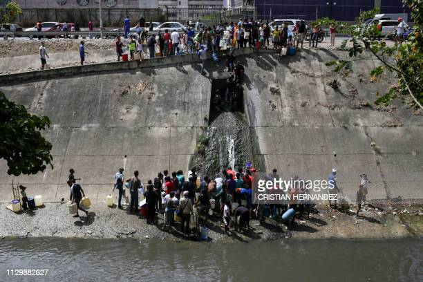 People collect water from a broken pipe flowing into a sewage canal at the Guaire river in Caracas on March 11 as a massive power outage continues...