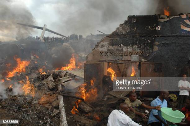 People collect water to put out a fire amid twisted debris as shops burn after a plane crash in Goma in the east of the Democratic of Congo on April...