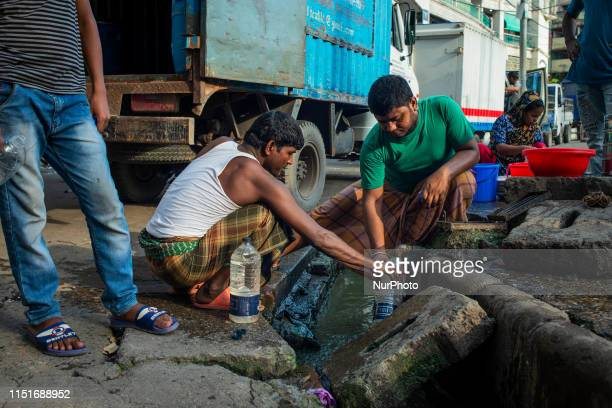 People collecting drinking water from a tap placed beside unhygienic drainage system at Dhaka Bangladesh on June 23 2019