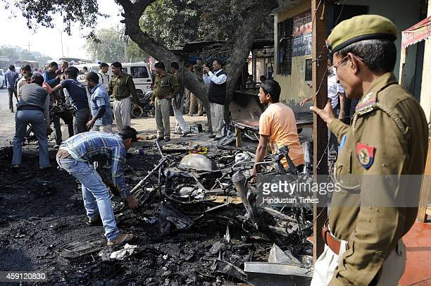 People collecting the remains of vehicles set ablaze by angry mob after their houses were demolished in anti-encroachment drive by Greater Noida...