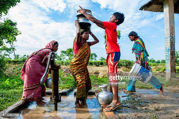 people collecting water from well in small village, bangladesh - bangladesh village stock photos and pictures