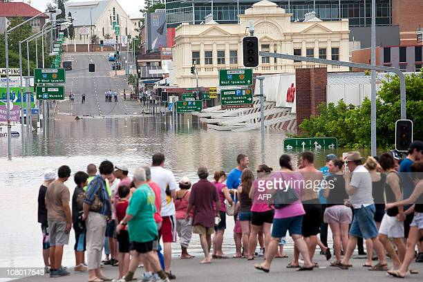People come out to view a flooded area around Limestone Street in the Ipswich city centre some 40 kms southwest of the Queensland city of Brisbane on...