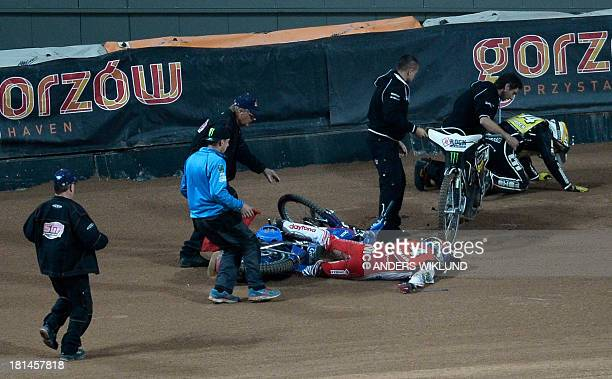 People come running to aid Poland's Tomasz Gollob who lies on the track while Great Britain's Tai Woffinden tries to get up after a collision between...