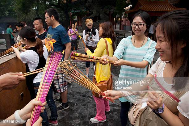 People come to pray and burn incense sticks at The Yonghe Temple also known as the Palace of Peace and Harmony Lama Temple the Yonghe Lamasery or...