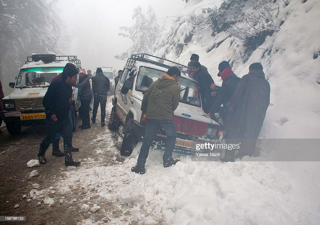 People come to the aid of a vehicle that lost its control on the roadside during a snowfall on December 29, 2012 in Gulmarg, 54 km (35 miles) to the west of Srinagar, the summer capital of Indian-administered Kashmir, India. With the second round of heavy snowfall in Kashmir valley, skiers from around the globe have descended on the ski resort of Gulmarg, known for long-run skiing, snow-boarding, heli-skiing and steep mountains. Gulmarg is located less than six miles from the ceasefire line or Line of Control (LoC) that divides Kashmir between India and Pakistan. As a sense of normalcy has started to return to this strife-torn region, various foreign governments, including the United Kingdom, have lifted the travel advisory to its citizens traveling to Kashmir, raising the hopes of the local tourism industry, officials said.