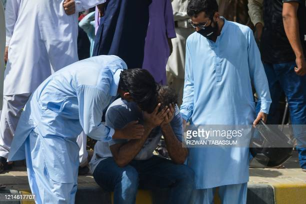People comfort a relative of a victim near the site after a Pakistan International Airlines aircraft crashed in a residential area in Karachi on May...