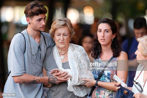 People comfort each other after a van ploughed into the crowd killing two persons and injuring several others on the Rambla in Barcelona on August 17...