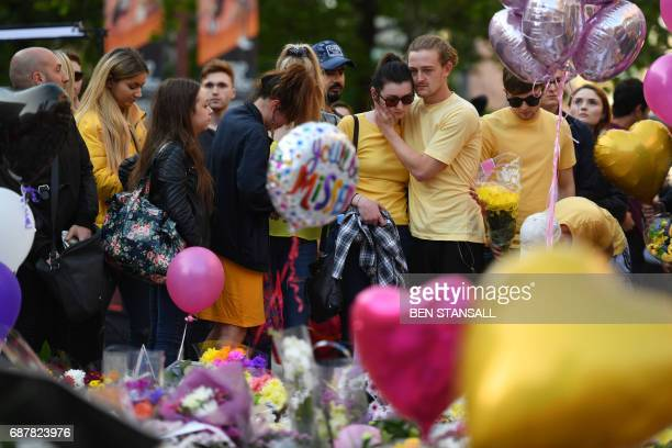 People comfort each other alongside a carpet of flowers and messages at St Ann's Square in Manchester northwest England on May 24 placed in tribute...