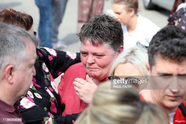 People comfort each other at a gathering condemning the overnight killing of journalist Lyra McKee near the scene of rioting violence in the Creggan...