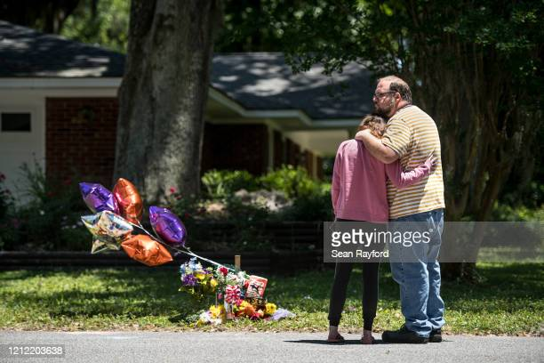 People comfort one another while looking at a memorial for Ahmaud Arbery near where he was shot and killed May 8, 2020 in Brunswick, Georgia. Gregory...
