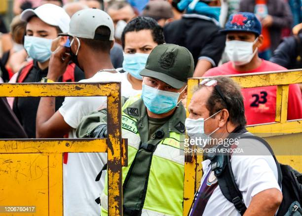 People coming from Venezuela with protective face masks as a precautionary measure to avoid contracting the new coronavirus, COVID-19, show hold...