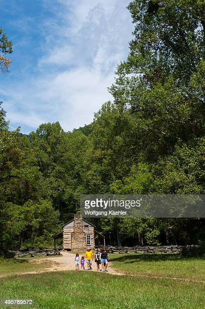 People coming from visiting the John Oliver cabin from the 1820s in Cades Cove Great Smoky Mountains National Park in Tennessee USA