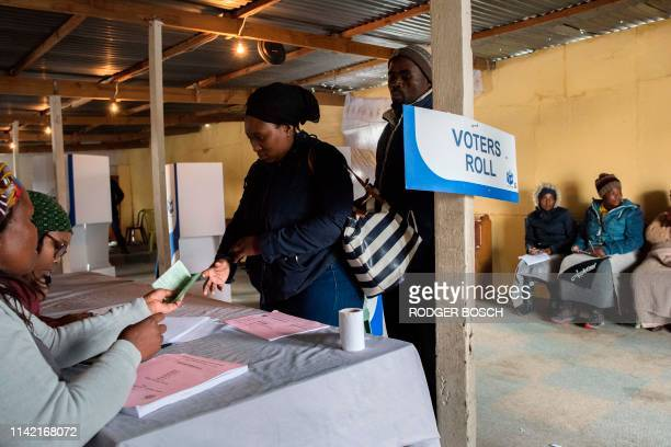 People coming to vote get their Identity documents checked by Independent Electoral Commission officials in a large shack being used as a voting...
