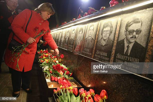 People commemorating the 30th anniversary of the Chernobyl nuclear disaster arrive to lay candles and flowers at a memorial to 27 men and three women...