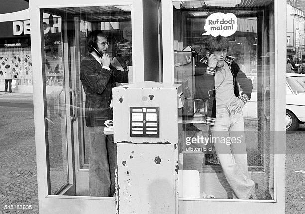 people communication a man and a teenager phone from two telephone boxes located side by side in front stands a letterbox man aged 30 to 40 years boy...