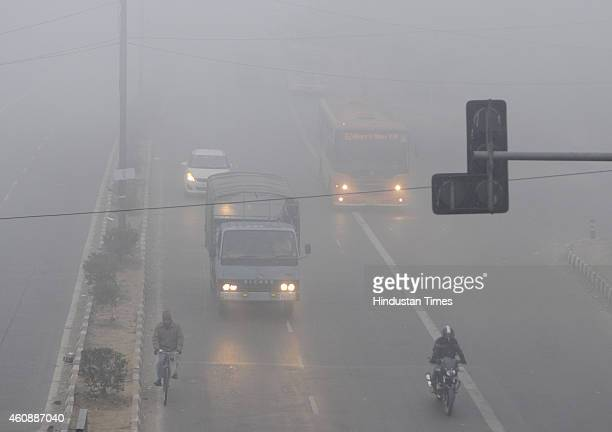 People commute amidst dense fog on a cold morning on December 29 2014 in New Delhi India It was a chilly morning with minimum temperature settling...